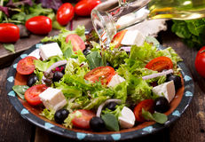Olive oil pouring into plate of salad stock image