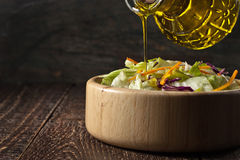 Olive oil pours from glass jug into a vegetable salad in a woode Royalty Free Stock Image