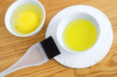 Olive oil and raw egg in a small ceramic bowls for preparing homemade spa face and hair masks. Ingredients for diy cosmetics. Royalty Free Stock Images