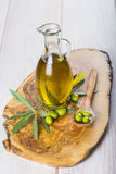 Olive oil with raw olives and leaves Stock Photo