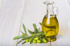 Olive oil with raw olives and leaves Stock Photos
