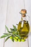 Olive oil with raw olives and leaves Royalty Free Stock Photography