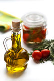 Olive oil with rosemary and cherry tomatoes. Olive oil with rosemary and preserved cherry tomatoes on a white background stock photos