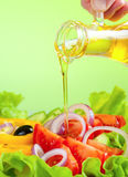 Olive oil stream and healthy fresh vegetable salad. Studio shot Royalty Free Stock Photography