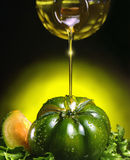 Olive Oil and tomato. A bottle pour oil on a green tomato stock image