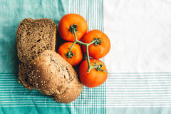 Olive Oil, tomato and brown bread on tablecloth Stock Photos