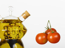 Olive oil and tomato cherry. Isolated picture of olive oil and cherry tomato on white background Royalty Free Stock Photos