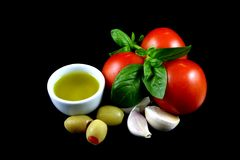 Olive Oil, Tomatoes, Garlic. Basil leaves, tomatoes, garlic buds, green stuffed olives and olive oil on black background Royalty Free Stock Images