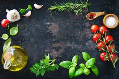 Olive oil, tomatoes, garlic, parsley, basil, spices on dark back. Mediterranean healthy cuisine. Olive oil, tomatoes, garlic, parsley, basil, spices on dark Stock Photo