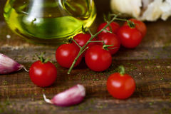 Olive oil, tomatoes and garlic on a wooden table. Closeup of some cherry tomatoes, some garlic cloves and a glass cruet with olive oil on a rustic wooden table Royalty Free Stock Photo