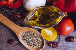 Olive oil, tomatoes and herbs on wooden table Stock Photography