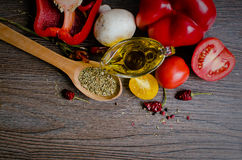 Olive oil, tomatoes and herbs on wooden table Royalty Free Stock Images