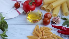 Olive oil, tomatos, basil and diffrent kinds of pasta on white wooden table. Ingredients for cooking pasta. Different kinds of pasta: penne, cannelloni stock video