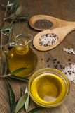 Olive oil, two spoons with salt and pepper on a wooden table royalty free stock photography