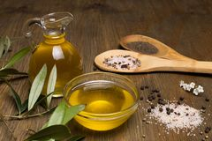 Olive oil, two wooden spoon with salt and pepper on a wooden table stock image
