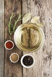 Olive oil and various spices onwooden rustic background: rosemary, paprika, black pepper. Top view. Olive oil and various spices onwooden rustic background stock photography