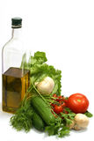 Olive oil with vegetables. Olive oil in transparent bottle with tomatos, cucumbers, mushrooms and green lettuce Stock Photos