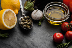Olive oil with vegetables , lemon and capers on the black stone table Stock Photo