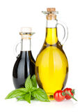 Olive oil, vinegar bottles with basil and tomatoes Stock Photos