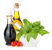 Olive oil and vinegar bottles with basil and tomatoes Royalty Free Stock Photography