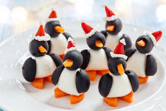 Olive penguins snack with santa hat Stock Photos
