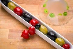 Olive in piatto con un vetro di martini nei precedenti Fotografia Stock Libera da Diritti