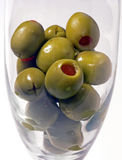Olive Reflections. Glass full of olives with funny face like olive at the bottim royalty free stock image
