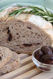 Olive and Rosemary Bread. A half loaf of rosemary bread with rosemary sprig sitting on a wood cutting board.  Ramekin of olives on the side Stock Photos