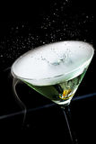 Olive splashing in a martini cocktail Royalty Free Stock Images