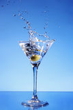 Olive splashing in a Martini glass stock photos