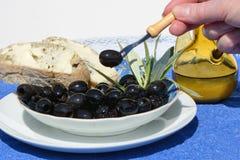 Olive sur la fourchette d'une cuvette photos stock