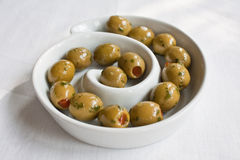 Olive Swirl. Stuffed green olives and a white swirl dish Royalty Free Stock Images