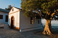 Olive tree and the church of Agios Ioannis Kastri at sunset, famous from Mamma Mia movie scenes, Skopelos Island. Greece royalty free stock photography