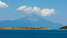 Olive trees on a small island in front of the holy mountains Athos Stock Image