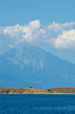 Olive trees on a small island in front of the holy mountains Athos Royalty Free Stock Image