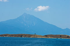 Olive trees on a small island in front of the holy mountains Athos Stock Images