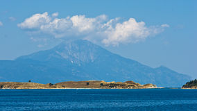 Olive trees on a small island in front of the holy mountains Athos Stock Photo