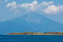 Olive trees on a small island in front of the holy mountains Athos Royalty Free Stock Photos