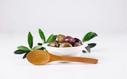 Olive in una ciotola ed in un cucchiaio di legno Fotografie Stock Libere da Diritti