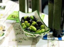 Olive verdi e nere in piatto della porcellana su una tavola Fotografia Stock