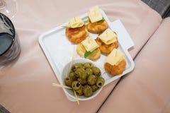 Olive verdi, fette di pane e formaggio Fotografia Stock