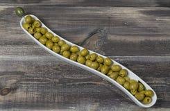 Olive verdi in vaso sulla tavola di legno Fotografia Stock