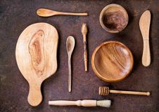 Olive wood cookware. Set of olive wood cookware over brown metal background. Top view Stock Photos