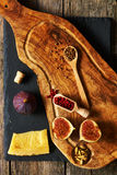 Olive wood cutting board with spices and fig Royalty Free Stock Images