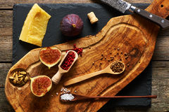 Olive wood cutting board with spices and fig Stock Images