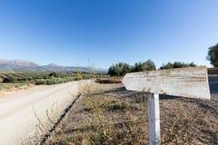 Oliveiras no montanhês acima da estrada de terra com sinal Imagem de Stock Royalty Free