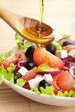 Olivenöl, das über Salat ausläuft Stockbilder