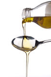 Olivenöl, das auf einen Löffel geschüttet wird Lizenzfreies Stockbild