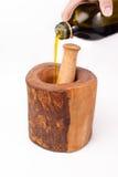 Olivenöl, das in olivgrünes hölzernes Sterblich und in Stampfe ausläuft Stockfotos