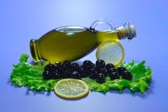 Olivenöl in der Flasche, in den schwarzen Oliven mit Zitrone und im Kopfsalat Lizenzfreie Stockfotos
